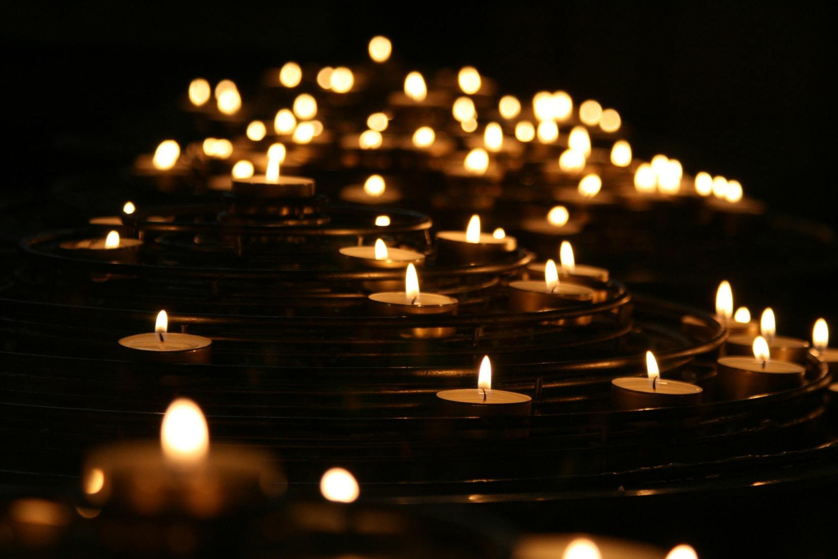 row of small candles in the dark used to signify grief and loss